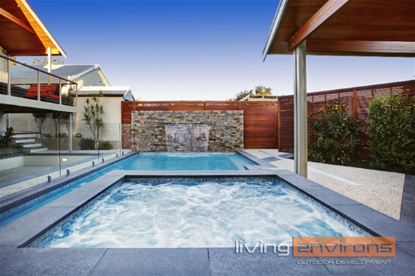 Custom concrete pool and spa with water feature wall. Designed and built by Living Environs.