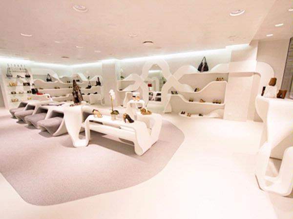 Staron® thermoformed into ribbon design shelving in Stuart Weitzman store. Photography by [v] style